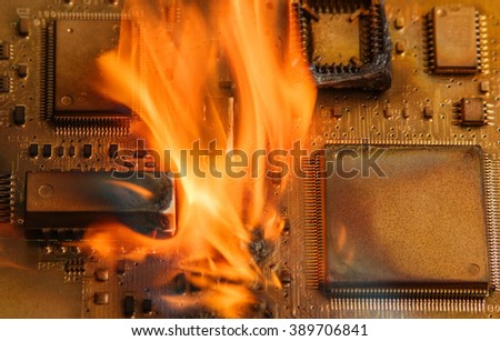 Burning circuit board with electronic components. Computer, technology, repair and fire protection concept. Low depth of field. - stock photo