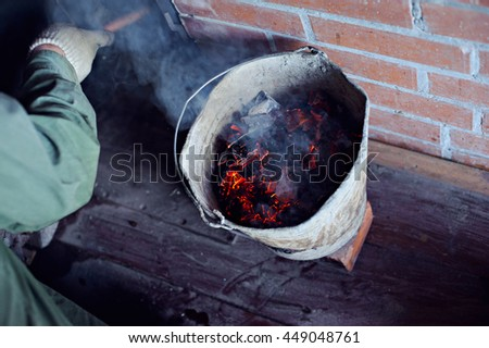 Burning coals in a bucket on a brick wall background and wood floor. - stock photo