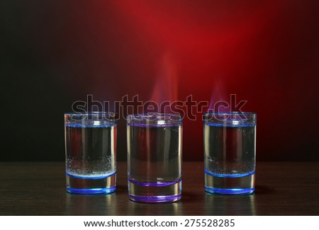 Burning cocktail in shot glasses on colorful background - stock photo