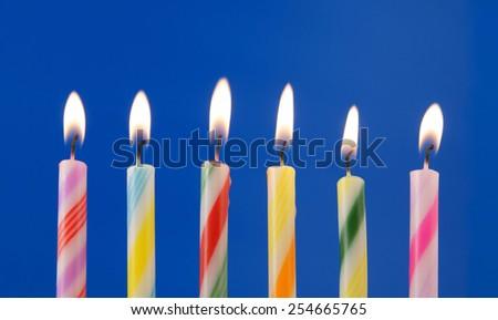 Burning colorful candles on blue background - stock photo