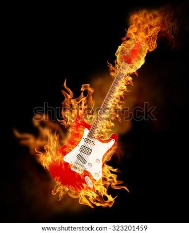 Burning electric guitar on black background. - stock photo