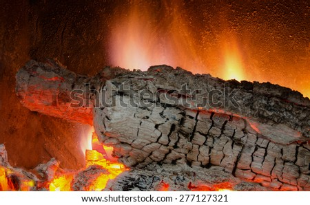 Burning embers of wood logs in a fireplace - stock photo