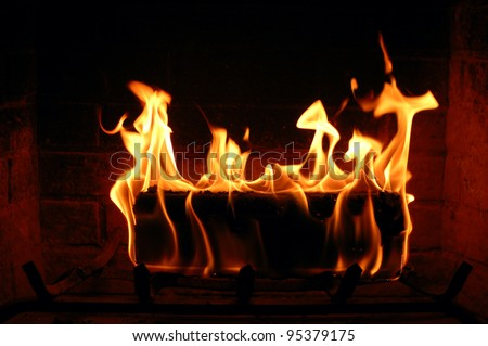 Burning fire log lighting the fireplace and heating a house - stock photo
