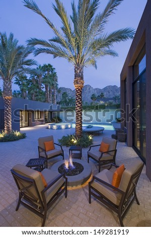 Burning fire pit surrounded by chairs on terrace of California home - stock photo