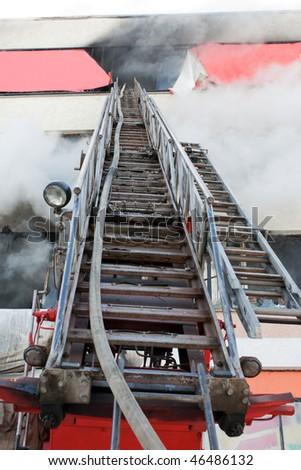 Burning fire, smoke, firefighters' emergency ladder - stock photo