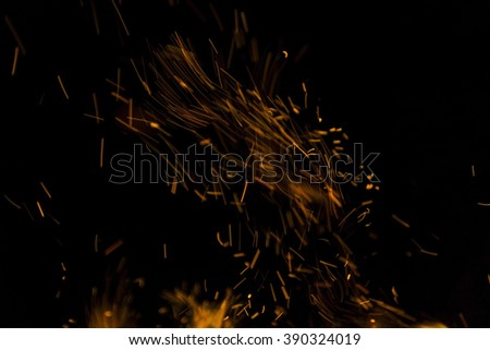 Burning fire with fiery orange flames, sparks and embers exploding into the air on a dark background with copy space - stock photo