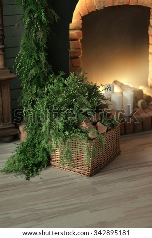 burning fireplace in the room, a large wicker basket with wood and pine needles - stock photo