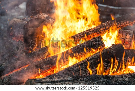 Burning firewood in bonfire with metal black kettle - stock photo