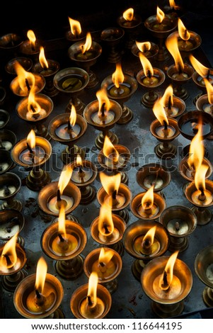 Burning flame of many Buddhist prayer lamps - stock photo