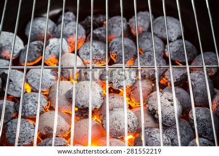Burning grill briquettes with clear empty grid - stock photo