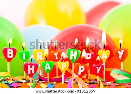 burning happy Birthday candles with balloons and confetti - stock photo