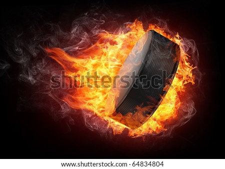 Burning hockey puck enveloped in fire flame isolated on black background.