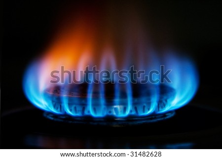 Burning hot blue yellow fire flames from a stove for cooking in a kitchen - stock photo