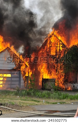 burning house  from the side garage starting to burn - stock photo