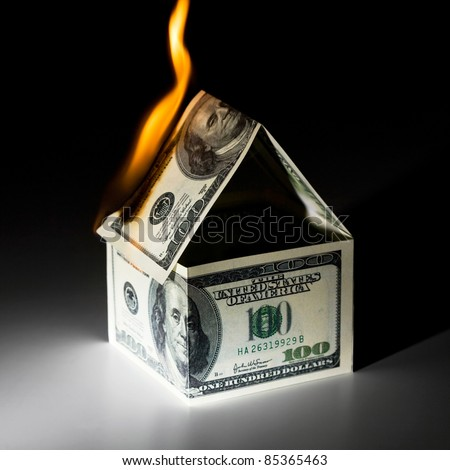 Burning house, made from dollars - stock photo