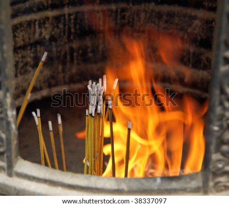Burning incense sticks with dancing flames in Ngong Ping buddhist monastery (Hong Kong China) - stock photo