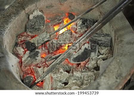 Burning iron in stove - stock photo