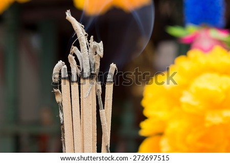 Burning joss stick in front of spirit house - stock photo
