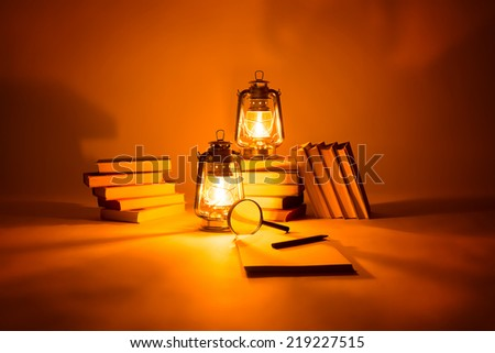 Burning kerosene lamps and books, concept magic of light   - stock photo