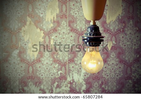 Burning lamp in the background of the old wall - stock photo