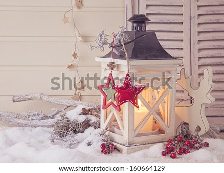 Burning lantern and christmas decoration on white background - stock photo
