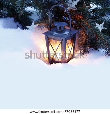 Burning lantern in the snow - stock photo
