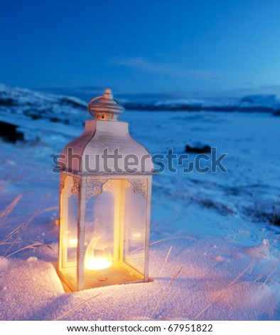 Burning lantern in the snow at dusk - stock photo