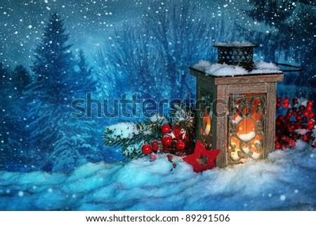 Burning lantern in the snow at night - stock photo
