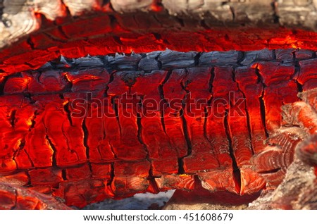 Burning log of wood in a fireplace close-up as abstract background. The hot embers of a burning wood log fire. Firewood burning on a grill. Texture fire bonfire embers.  Smoldering fire - stock photo
