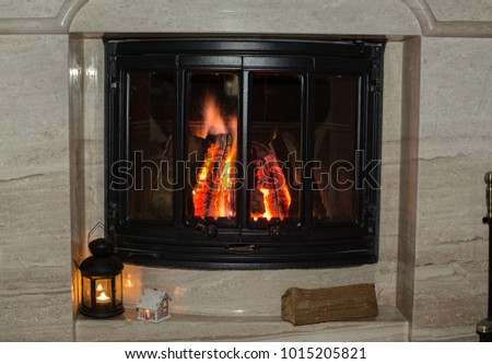 Burning logs in a glass door of a marble fireplace. Lantern with a candle.