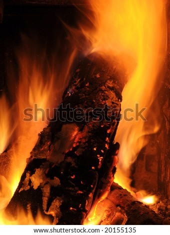 Burning logs in a tiled stove make a cozy warmth - stock photo