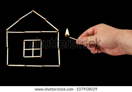 Burning match in hand and house isolated on black background - stock photo