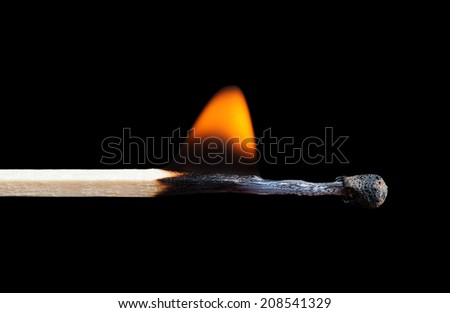 Burning match on black background - stock photo