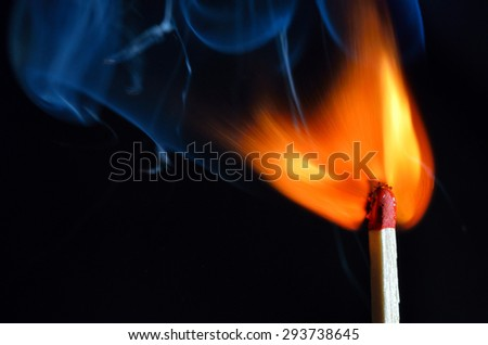 Burning match over black background