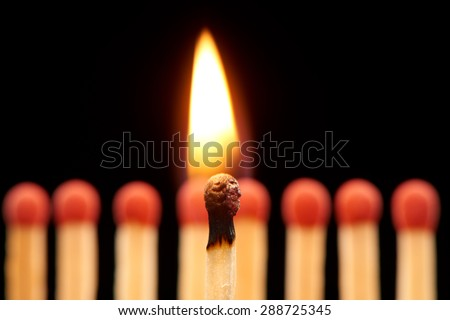Burning match standing in front of defocused set of eight red wooden matches, isolated on black background - stock photo