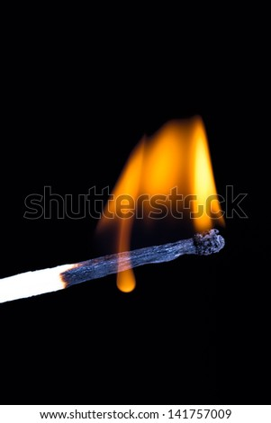 Burning match with flame on black background.