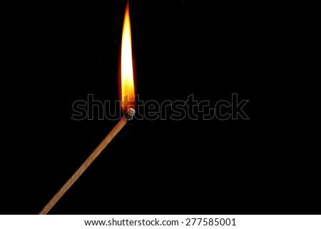 Burning match with smoke on dark background - stock photo