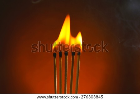 Burning matches with smoke on dark color background - stock photo
