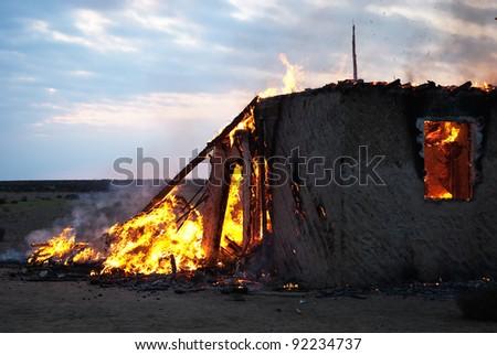 Burning old abandoned house at dusk - stock photo