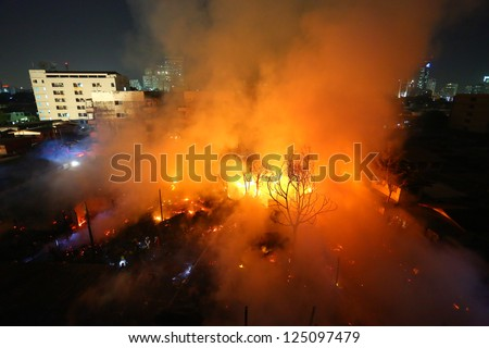 Burning old abandoned house in the city at dusk - stock photo