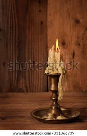 burning old candle vintage bronze candlestick on wooden background.  - stock photo