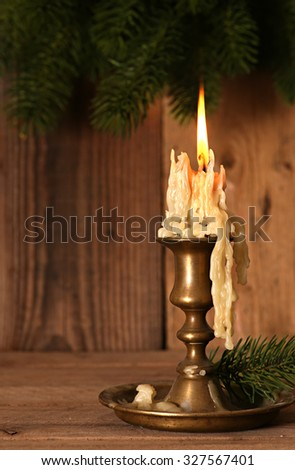 Burning old Candle Vintage Bronze candlestick on wooden background. Spruce branches. Christmas background. - stock photo