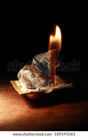 Burning one hundred dollar bank note in ashtray on dark background - stock photo