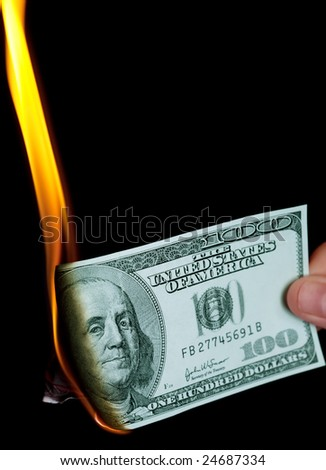 Burning one hundred dollars bank-note with portrait of Benjamin Franklin - stock photo