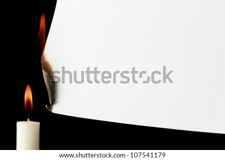 Burning paper with candle on a black background - stock photo