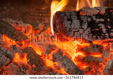 Burning piece of wood in fireplace close-up - stock photo