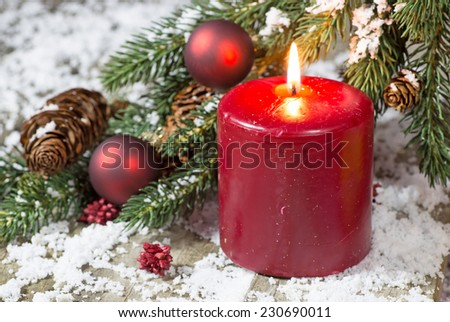 Burning red holiday candle with Christmas decorations - stock photo