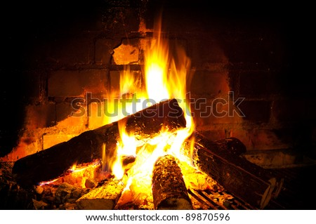 burning round logs in fireplace against brick smoked wall - stock photo