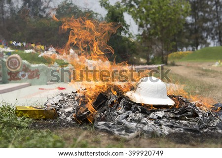Burning Silver and gold paper and hat to worship ancestor in Chinese culture, the Qingming Festival at graveyard Cemetery  - stock photo