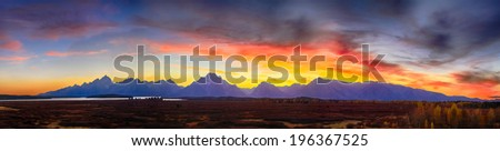 burning sky and Grand Teton mountains at sunset.